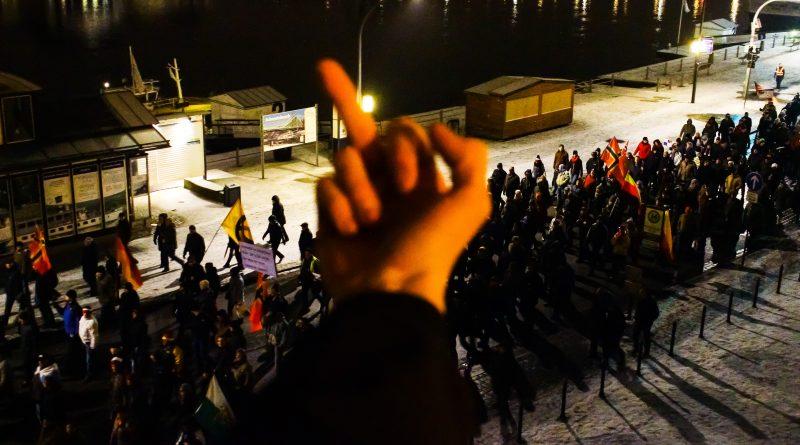 Ein Teilnehmer der Gegendemonstration zeigt den Pegida Demonstranten seine Meinung
