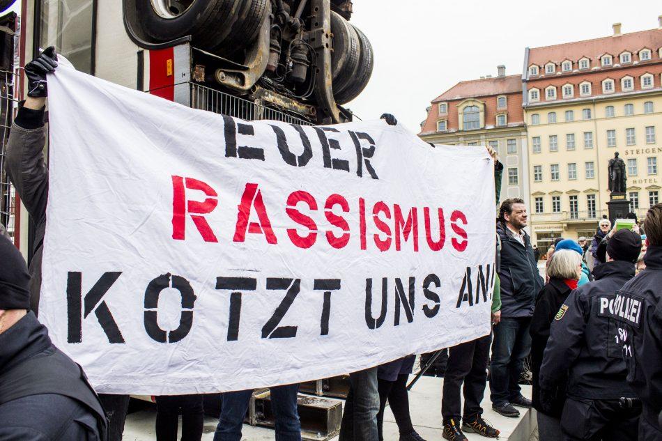 Einige Linke Demonstranten postierten sich mit einem Banner vor dem Kunstwerk, wurden aber nach kurzem von der Polizei hinter die Busse geschoben