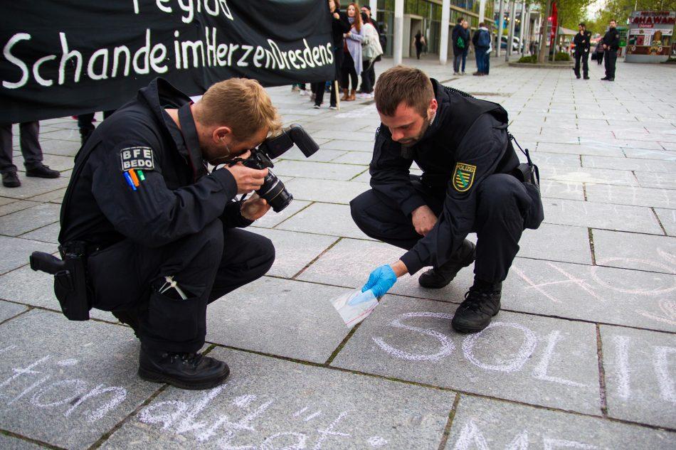 Beamte stellen Überreste einer Glasampulle sicher, die auf die Demonstration von Nationalismus raus aus den Köpfen geworfen wurde