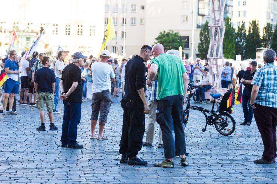 Ein Teilnehmer mit einem Tattoo der Schwarzen Sonne begrüsst einen Ordner von Pegida