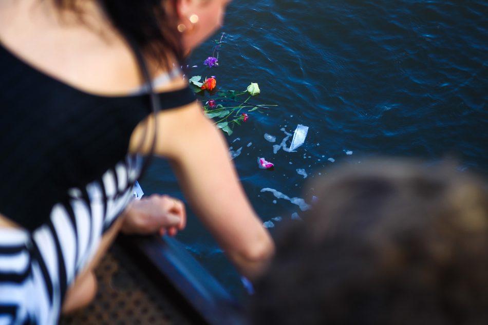 Teilnehmer der Seebrücke lassen Blumen und symbolische Papierboote in die Elbe