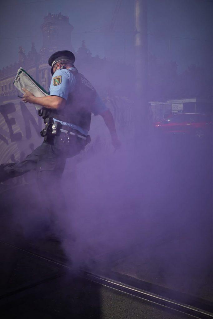 Der Polizist tritt hier den Rauchtopf den er als Beweiß sichern wollte gezielt zurück zu den Demonstranten