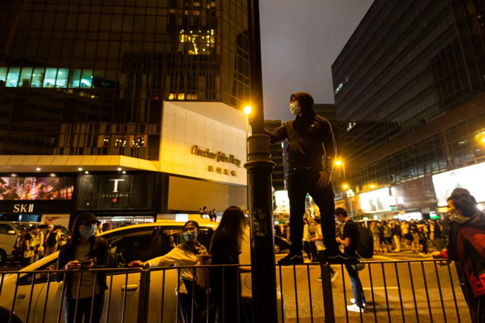 Ein Demonstrant hält ausschau ob Verstärkungen der Polizei kommen