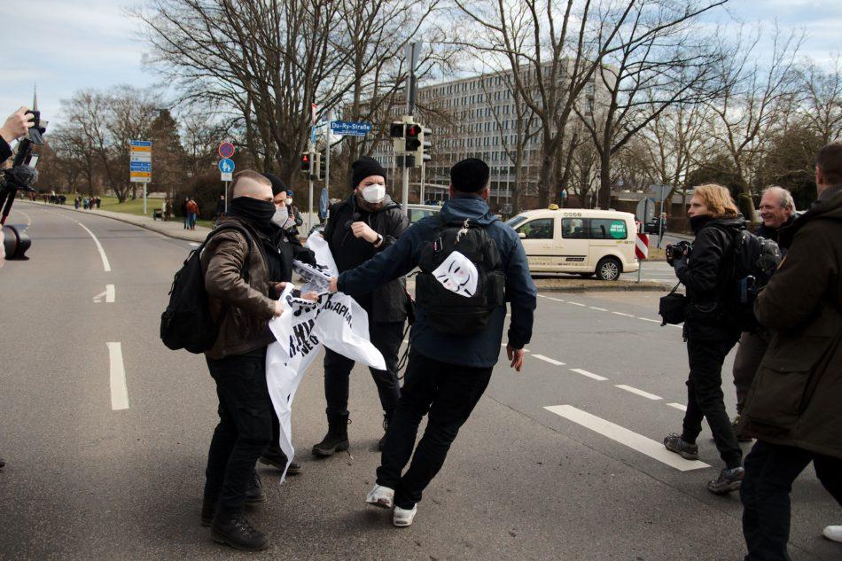 """Ein """"Querdenker"""" versucht den beiden Gegendemonstranten ihr Transparent zu entreißen"""