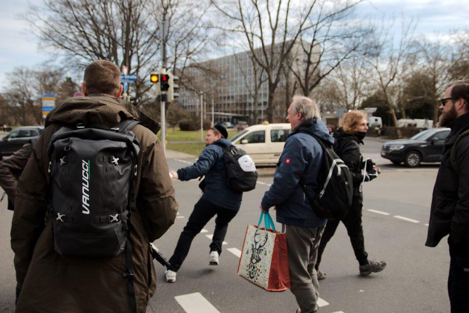 """Ein """"Querdenker"""" versucht den beiden Gegendemonstranten ihr Transparent zu entreißen, die Person im Vordergrund tritt kurz danach einen der Gegendemonstranten"""