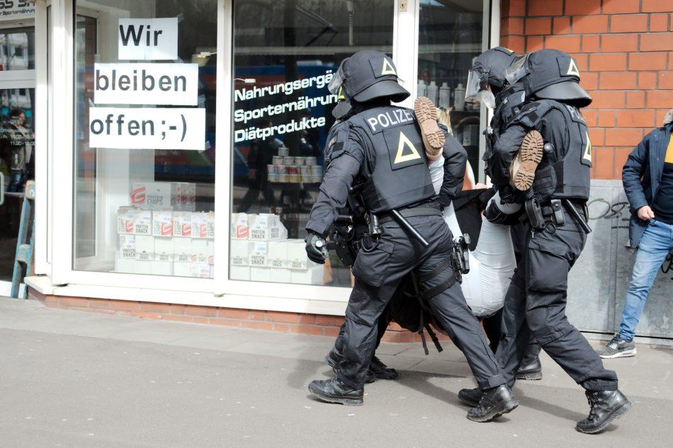 Ein Person wird von Polizisten weg getragen