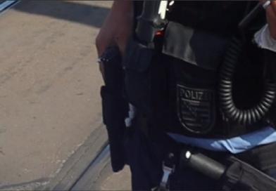 """Ein Dresdner Polizist """"Sichert"""" seine Dienstwaffe bei einer Demonstration"""